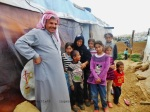 Mohanned and some of his 13 family members outside his makeshift home in Fayda refugee camp.