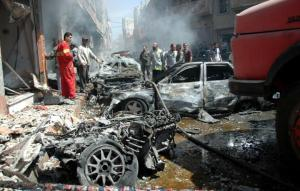 Emergency personnel and civilians inspect the site following a car bomb explosion in the Abbasiyah neighborhood of Syria's central city of Homs on April 29, 2014. (Photo: AFP / STR)