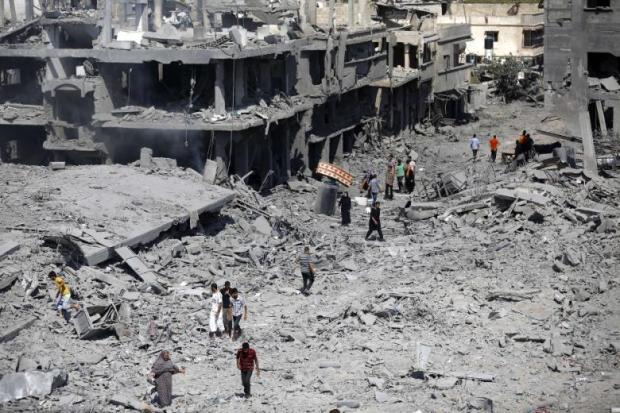 Palestinians walk on the rubble as they enter the northern district of Beit Hanoun to check their homes in the Gaza Strip during a humanitarian truce on July 26, 2014. (Photo: AFP - Mohammed Abed)