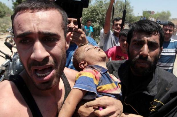 Relatives carry the body of a boy killed in an Israeli air strike on Gaza on July 9, 2014. (Photo: UPI - Ashraf Amra)