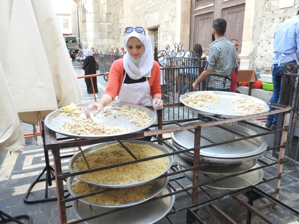 Behind the Umayyad Mosque in Old Damascus, one of tens of volunteers daily helps prepare the Iftar (fast-breaking) meals that the Saaed Association was serving to impoverished Damascus residents, even delivering to those unable to pick up meals themselves. Starting with 3,000 recipients, by the end of Ramadan, the volunteers were providing 10,000 meals daily in Damascus alone, with another combined 7,000 meals prepared in Hama and Homs. https://www.mintpressnews.com/damascus-life-returns-5-years-after-nato-destabilization-efforts/218601/