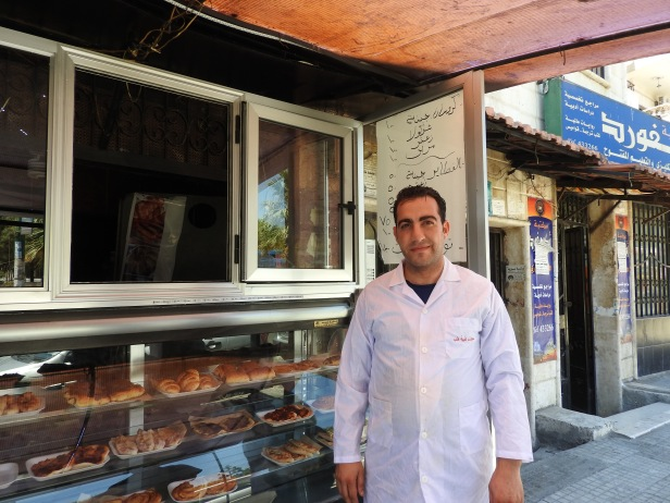Croissant shop owner is displaced from Aleppo, from one of the first areas to be infested by terrorists. He lost he three apparently very-well known and loved croissant/bakery shops, all the equipment, his home and all furnishings when he and family fled the terrorists to Latakia. His personal loss also of course affected the 10 employees he had in Aleppo. Here, he worked for about 4 months in Jableh before opening his first croissant shop in Latakia, which has since blossomed into two apparently very popular croissant shops. More here: https://ingaza.wordpress.com/2016/08/11/updates-from-on-the-ground-in-syria-june-to-august-11/ or here: https://www.facebook.com/EvaBoBeeva/posts/1244053205604671