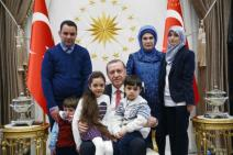 Turkey's President Recep Tayyip Erdogan,accompanied by his wife Emine, standing 2nd right, poses for pictures with the family of Bana Al-Abed, seated on his lap left, 7, from Aleppo, Syria, at his Presidential Palace in Ankara, Turkey, Wednesday, Dec. 21, 2016. The Syrian child who became the civilian face of Aleppo – 7-year old Bana Al-Abed whose tweets of life under siege in Aleppo went viral and who was evacuated from Aleppo was greeted along with her family by Erdogan on Wednesday. Mother Fatemah Al-Abed, right, and father Ghassan Al-Abed, name of other sibling is not available.(Presidency Press Service via AP, Pool)